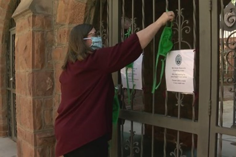 The Very Rev. Kristina Maulden hangs masks for the community