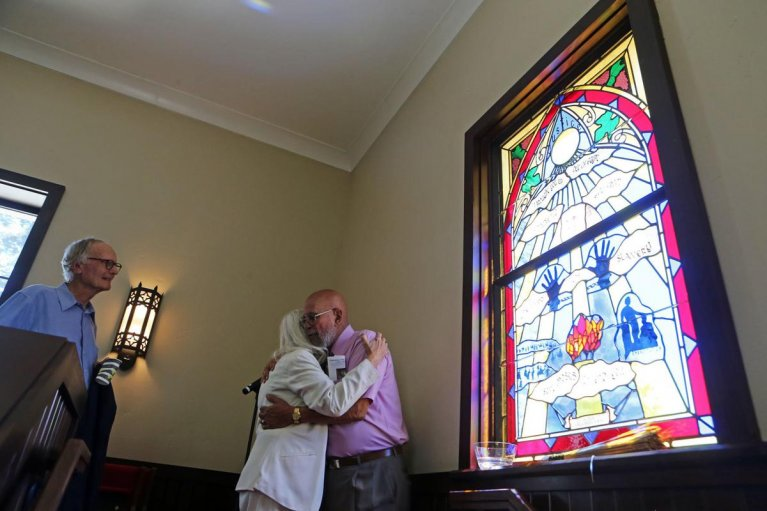 "Whitney J. LeBlanc embraces a fellow member of Grace, St. Helena, shortly after the dedication of ""Justice,"" the newest of stained glass windows he has crafted for the church since moving to Napa Valley in 1996."