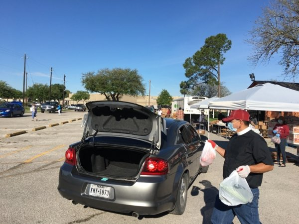 The Rev. Pedro López, vicar of Iglesia Episcopal San Pedro in Pasadena, Texas, helps distribute food during its food drive.